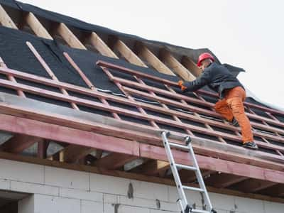 This is a picture of a worker on top of the roof of a restaurant. The worker has ripped off the shingles and will be starting roof installation. This picture was taken in Terre Haute, IN.