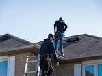 This is a picture of two guys climbing a residential roof to inspect the roof for potential installation. This picture was taken in Terre Haute, Indiana.